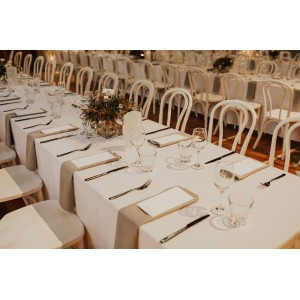 Trestle tables with white linen, accompanied by our white bentwood chairs