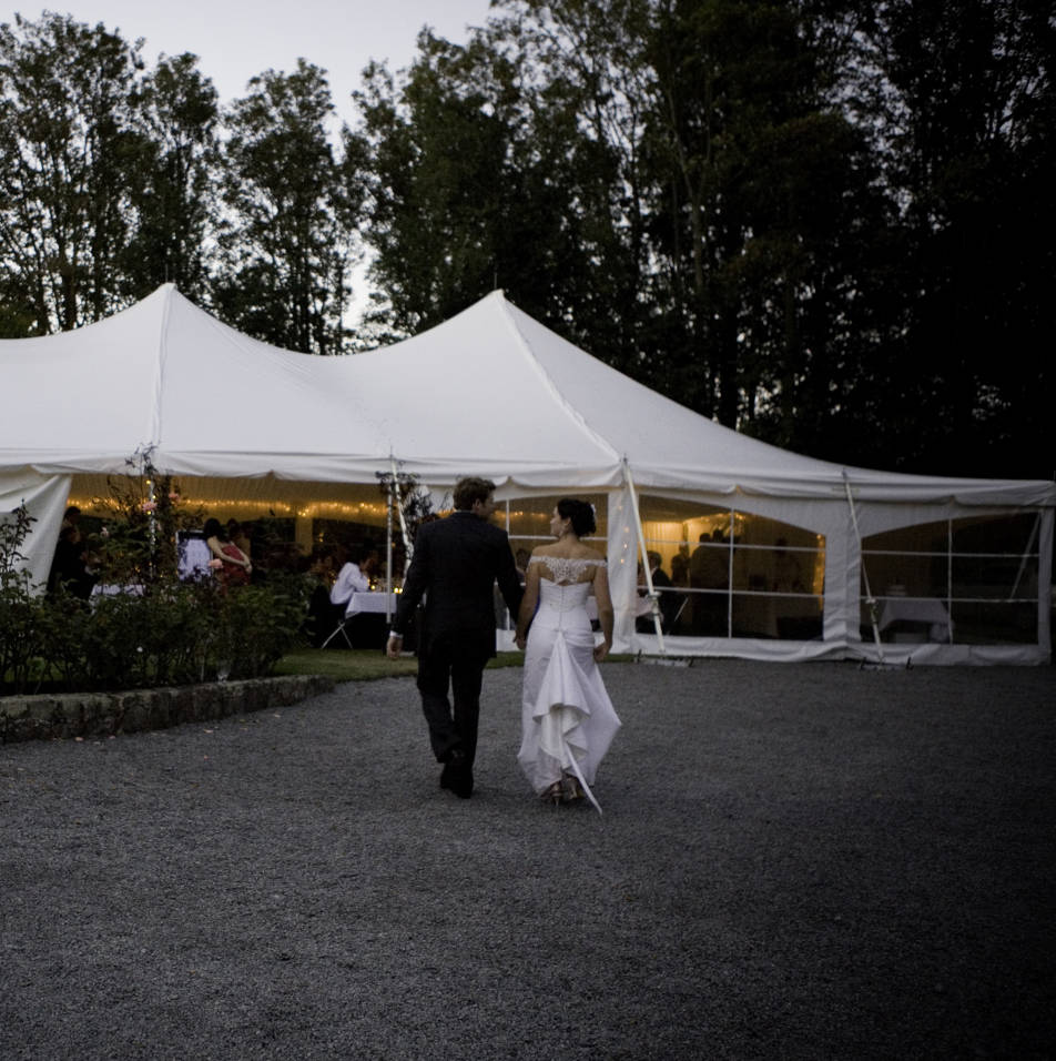Bride and groom walk to their marquee wedding venue